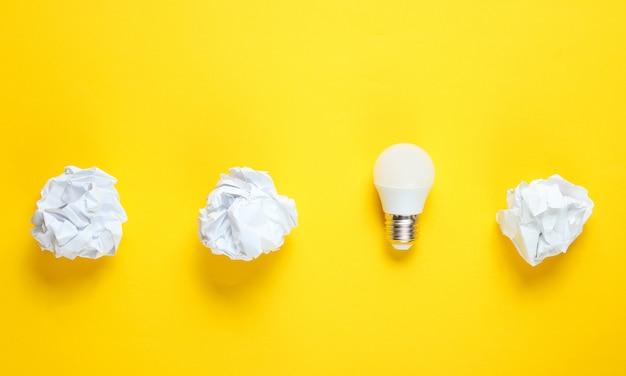 Energiebesparende lamp en verfrommeld papier ballen op gele tafel. minimalistisch bedrijfsconcept, idee. bovenaanzicht
