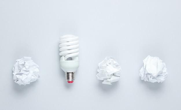 Energiebesparende lamp en verfrommeld papier ballen op grijze tafel. bovenaanzicht