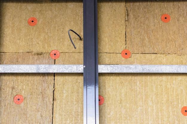 Energiebesparende technologie: platen van minerale wol op de zijwand, tussen de metalen profielen voor bevestiging van de geventileerde gevel.