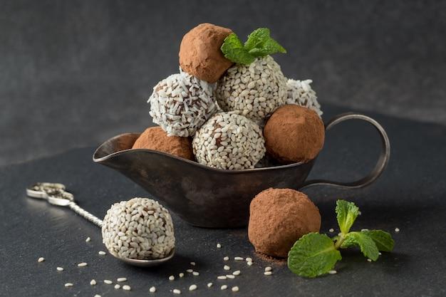 Energiebeten met cacaopoeder, sesamzaadjes en kokosnootvlokken in juskom op grijze tafel