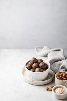Energiebolletjes van havermout, noten en gedroogd fruit op een lichtgrijze kleur