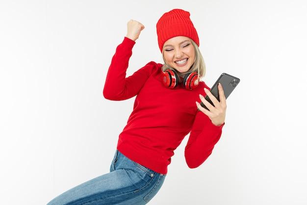 Energiek charismatisch blond meisje met een smartphone en koptelefoon