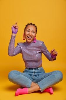Energiek positief meisje met een donkere huid en een goed humeur zit gekruiste benen, heft armen op en beweegt met het ritme van de muziek, kijkt vrolijk opzij, draagt trui, jeans en sokken, geïsoleerd over gele muur