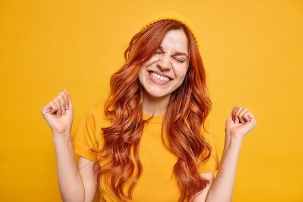 Energiek vrolijk millennial meisje lacht vrolijk balt vuisten van vreugde viert succesvolle dag heeft natuurlijk rood golvend haar draagt hoed casual t-shirt