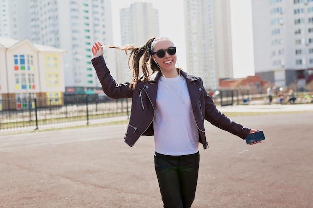 Energieke aantrekkelijke vrouw gekleed wit t-shirt, leren jas en zwarte zonnebril