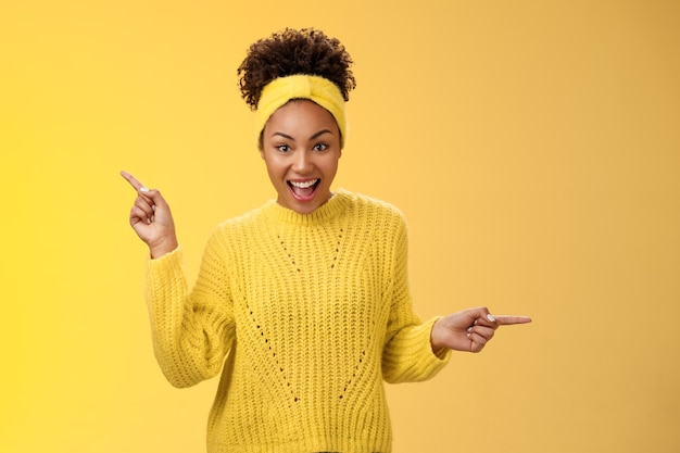 Energieke actieve charismatische afro-amerikaanse vrouw afro kapsel in trui hoofdband schreeuwen gefascineerd enthousiast wijzend links rechts indruk op verschillende geweldige keuzes, producten plukken.