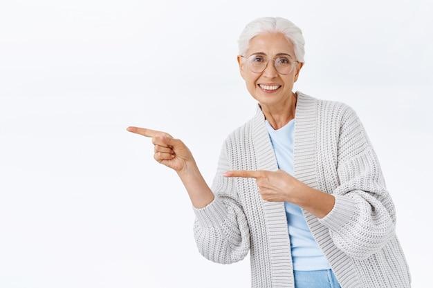 Energieke, actieve, gelukkige en gezonde senior dame die graag een geweldige promo laat zien, naar links wijst en buigt om haar aanbeveling en positieve houding ten opzichte van een goede deal uit te drukken, tevreden glimlachend