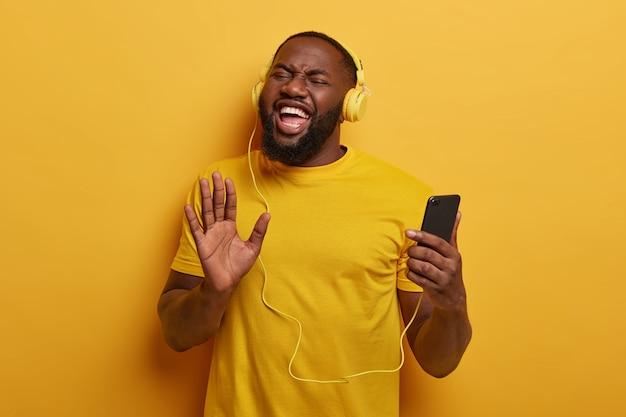 Energieke afro-amerikaanse man trekt handpalm naar camera, gebruikt smartphone en headset voor het luisteren naar radio- of audiotracks in de afspeellijst, stimuleert de stemming met favoriete liedje