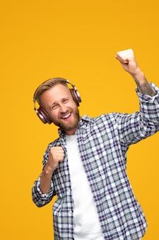 Energieke bebaarde hipster-man in casual geruit overhemd en draadloze koptelefoon