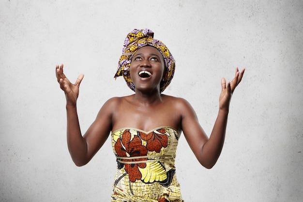 Energieke blije vrouw met een donkere huid die een sjaal op het hoofd draagt en een modieuze jurk die omhoog kijkt en haar handen opheft van opwinding, dankbaar aan god voor levensreddende. dankbare afrikaanse vrouw van middelbare leeftijd