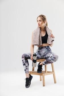 Energieke blonde vrouw gekleed in sportkleding met handdoek over nek zittend op stoel na training in sportschool geïsoleerd over witte muur