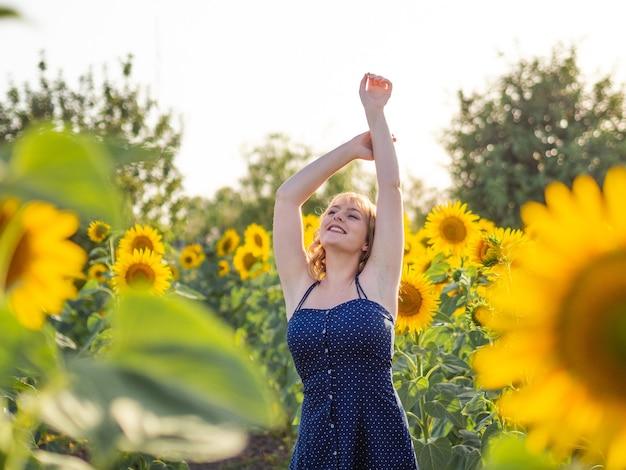 Energieke bochtige vrouw ontspannen in het zonnebloemveld