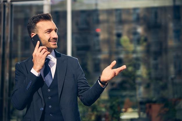 Energieke brunette zakenman die buiten in mooi pak met stropdas blijft terwijl hij telefoneert en hand opsteekt