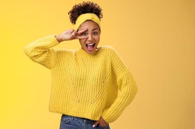 Energieke charmante duizendjarige afro-amerikaanse vrouwelijke student in gele trui hoofdband show overwinning vredesgebaar voel me gelukkig opgewonden genietend van discofeest vrolijk glimlachen, vreugde.