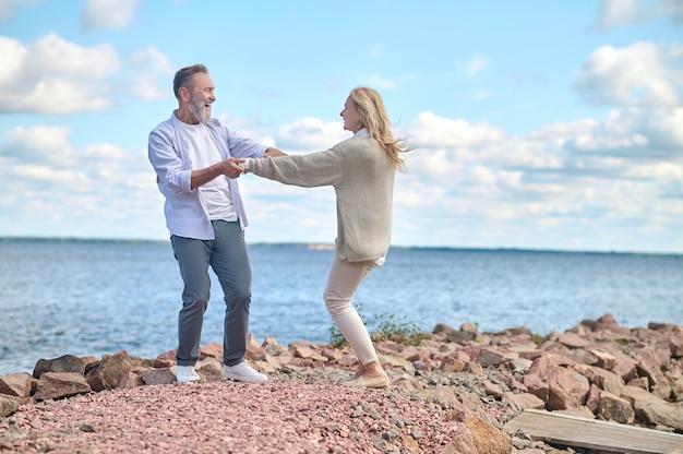Energieke en gelukkige man en vrouw in de buurt van zee