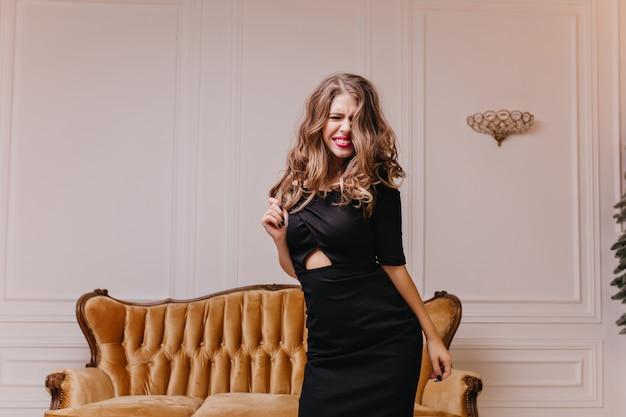 Energieke, fantastische krullende bruinharige vrouw heeft plezier en gelukkig poseren in nieuwe modieuze jurk. portret van glimlachende vrouw binnenshuis