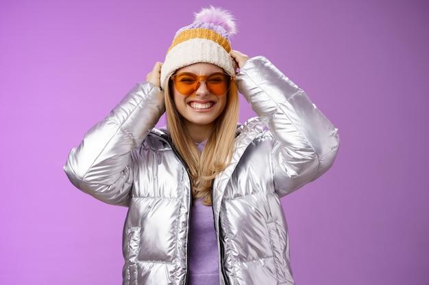 Energieke gedurfde brutale jonge aantrekkelijke vrouw met leuke vrienden winterreis leren snowboarden glimlachend brutaal genieten van vakantie opgezette hoed dragen van een zilveren warme jas zonnebril, paarse achtergrond.