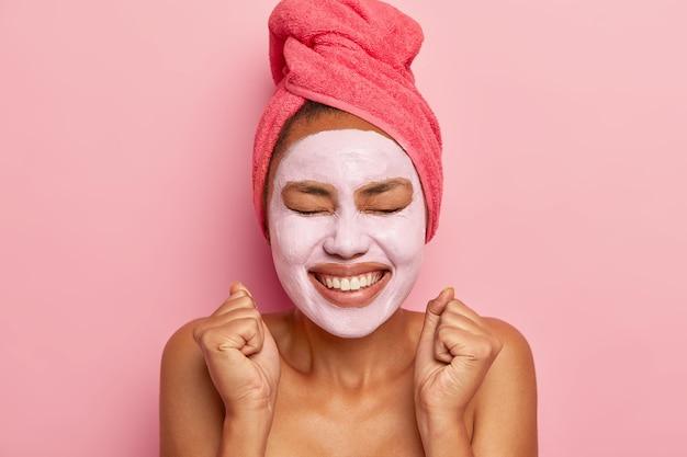 Energieke gelukkige vrouw draagt een kleimasker op het gezicht, een handdoek om het haar gewikkeld, glimlacht breed, balt vuisten van plezier, geïsoleerd over roze muur