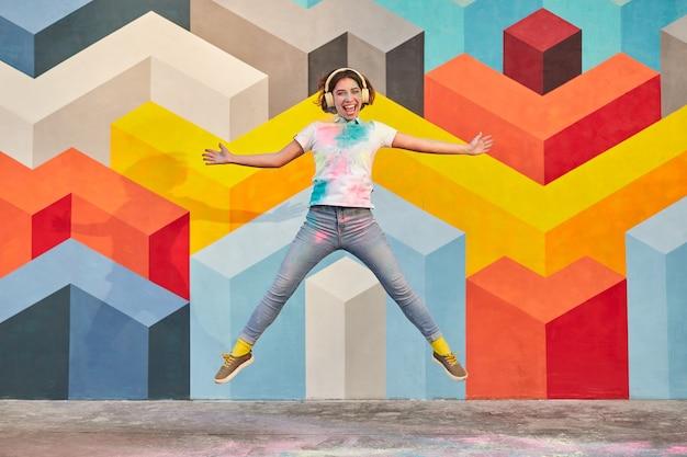 Energieke jonge vrouw die met hoofdtelefoons dichtbij kleurrijke muur springt