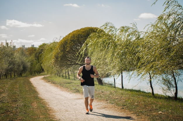 Energieke jongeman doet oefeningen buiten in het park om zijn lichaam in vorm te houden.