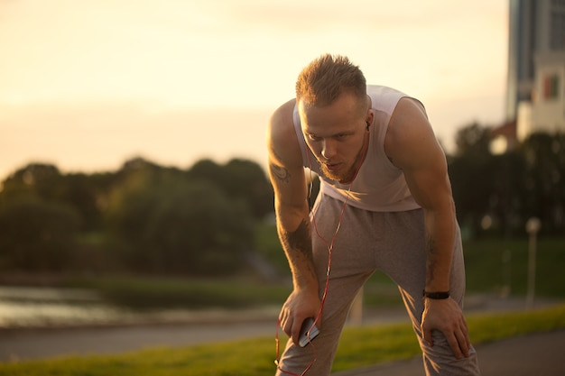 Energieke jongeman doet oefeningen en loopt buiten met telefoon en muziek en loopt in het park om zijn lichaam in vorm te houden.