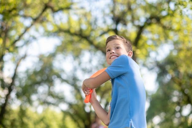 Energieke jongen die tennisracket slingert in de natuur