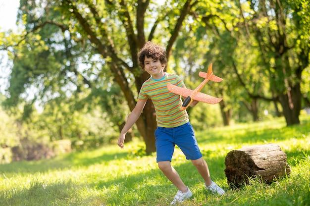 Energieke jongen spelen met speelgoedvliegtuig op gazon