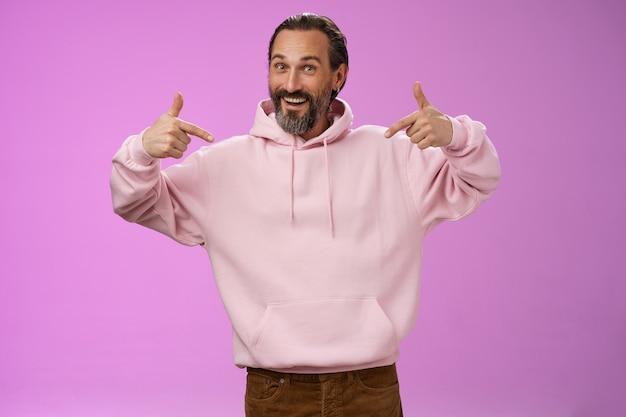 Energieke knappe coole hipster volwassen man baard grijs haar rimpels wijzend zichzelf opscheppen prestaties willen deelnemen hulp bieden, suggereren zijn kandidatuur, staande paarse achtergrond.