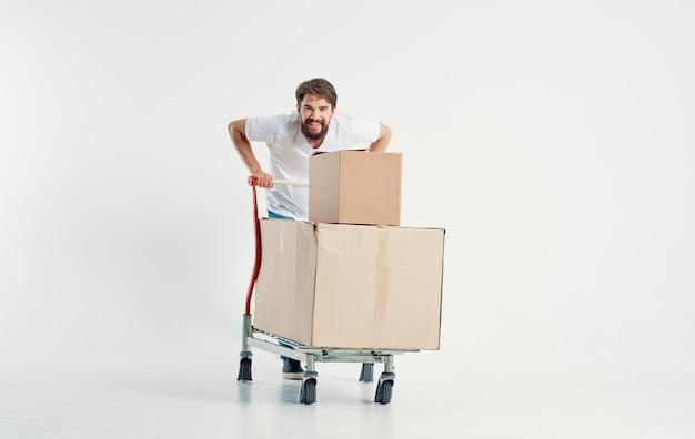 Energieke koerier met kartonnen dozen die zware lading lichte achtergrond vervoeren