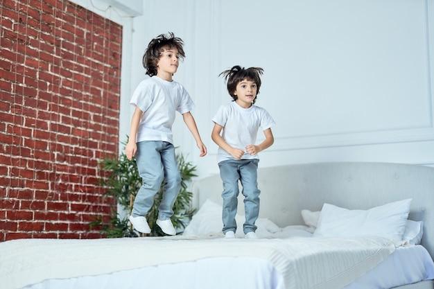 Energieke latijns-amerikaanse jongens, broers die samen plezier hebben, thuis op het bed springen. kinderen, geluk, familieconcept