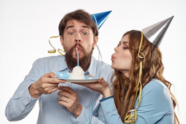 Energieke man en vrouw met een taart en in hoeden vieren een verjaardag op een lichte achtergrond