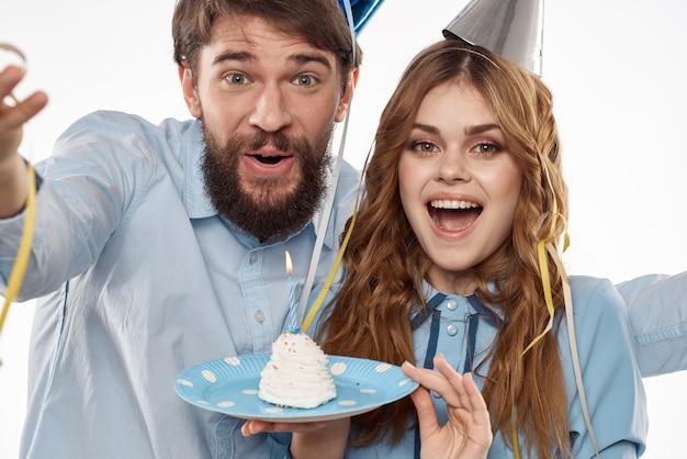 Energieke man en vrouw met een taart en in hoeden vieren een verjaardag op een lichtje
