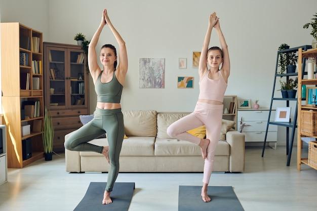 Energieke moeder en haar tienerdochter balanceren op één been tijdens het doen van boom vormen in de woonkamer