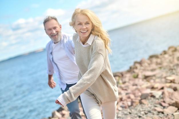 Energieke mooie vrouw en man lopen in de buurt van zee