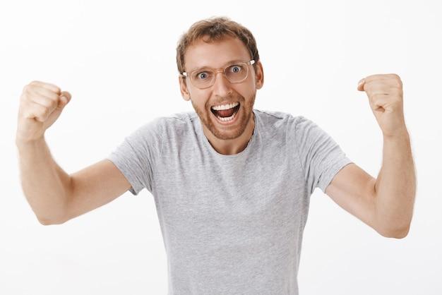 Energieke opgewonden en enthousiaste teamleider in bril en grijs t-shirt die vuisten opstak van gejuich, schreeuwend van het ondersteunen en aanmoedigen van werknemers die geamuseerd over een witte muur staan