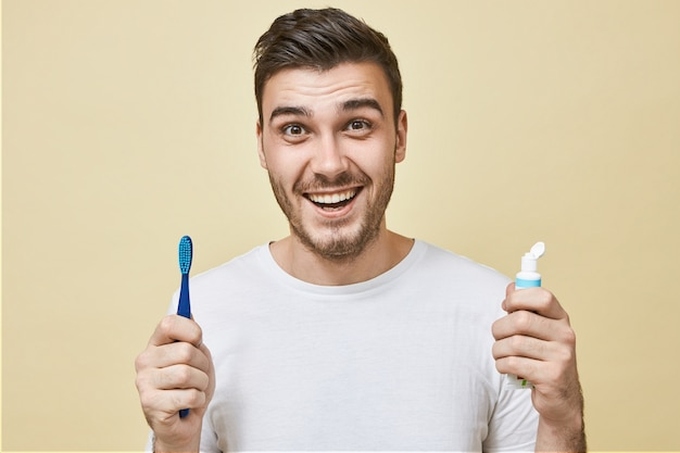 Energieke positieve jongeman met stoppels poseren met tandenborstel en bleekpasta breed glimlachend met perfecte witte tanden. gezonde gewoontes, dagelijkse routine en tandheelkundige zorg