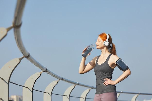 Energieke roodharige rijpe vrouw in draadloze hoofdtelefoons drinkwater na een training aan de rivier