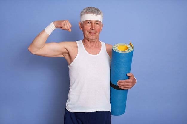 Energieke senior man heeft fysieke training, houdt yogamat vast, toont biceps en zijn kracht