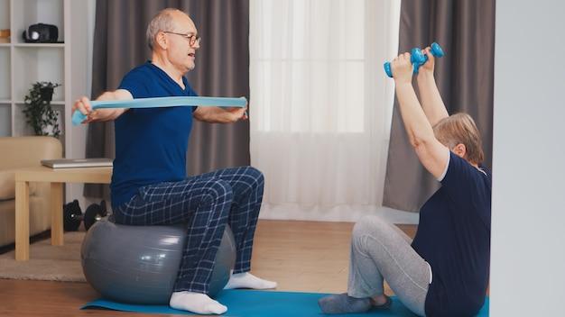 Energieke senior paar training in huis met behulp van halters en stabiliteitsbal. oude persoon gezonde levensstijl oefening thuis, training en training, sportactiviteit thuis