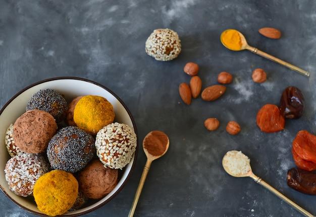 Energieke snoepjes gemaakt van gedroogde abrikozen, dadels, amandelen, hazelnoten, gedroogde noten, zaden, gedroogd fruit en honing. zelfgemaakte nuttige snoepjes. rauwe en veganistische snoepjes. energieballen
