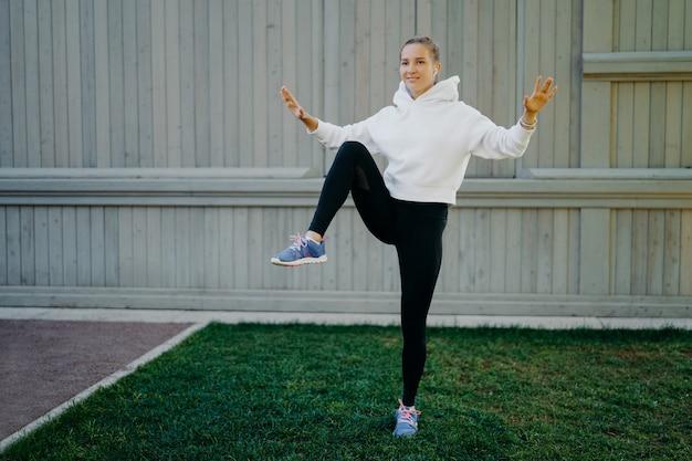Energieke sportvrouw heeft trainingsroutines op één been, laat zien dat haar uithoudingsvermogen opwarmt voordat ze gaat joggen, gekleed in hoodie-legging en trainers buiten trainen. sport en motivatie concept