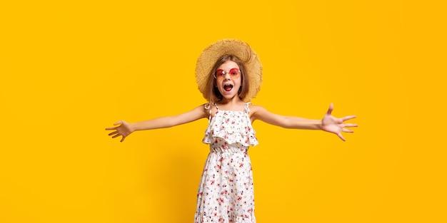 Energieke tiener in stijlvolle zomerjurk en strohoed die schreeuwt en naar de camera kijkt