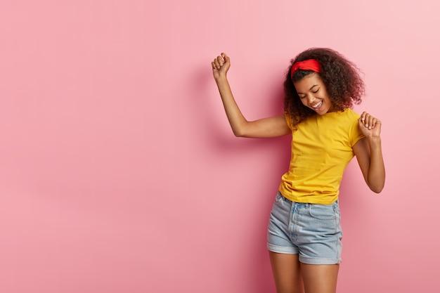 Energieke tienermeisje met krullend haar poseren in gele t-shirt