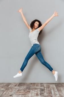 Energieke vrouw 20s in gestreepte t-shirt en jeans springen met handen overgeven in lucht over grijs