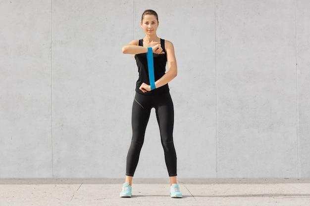 Energieke vrouw gekleed in zwarte top en legging, sportschoenen, strekt haar handen uit met fitnessgom, bereidt zich voor op wedstrijden