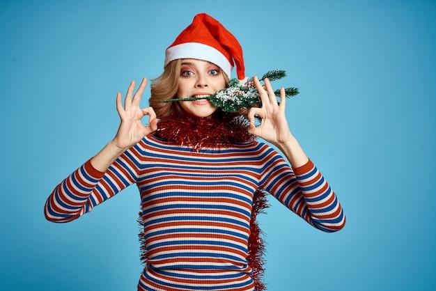 Energieke vrouw met kerstboom handen boomtakken model rode hoed