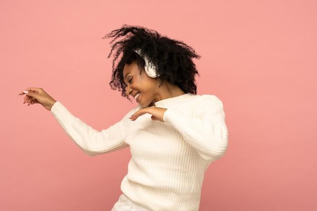 Energieke vrouw zingt mee draagt draadloze koptelefoon heeft een goed humeur geïsoleerd op roze