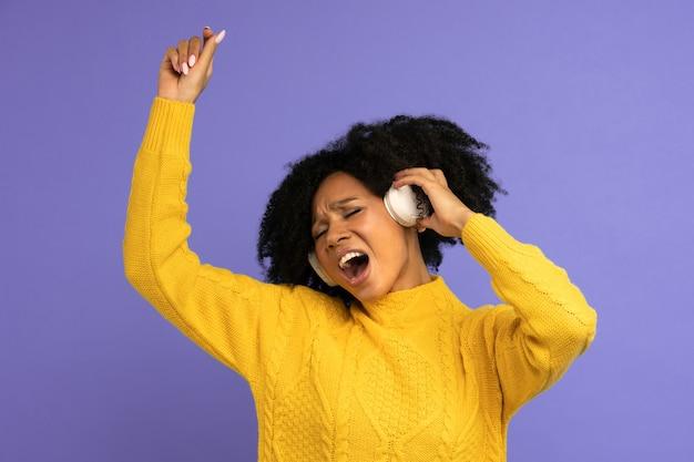 Energieke vrouw zingt mee terwijl ze naar muziek luistert via een koptelefoon