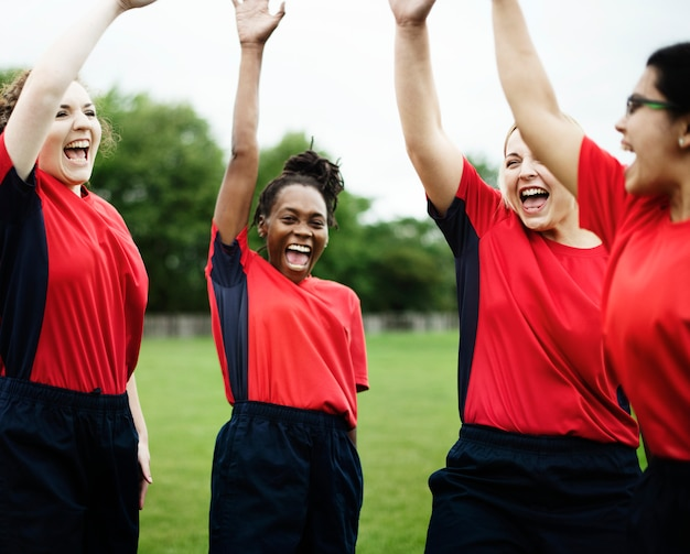 Energieke vrouwelijke rugbyspelers die samen vieren
