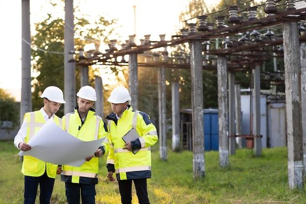 Energiespecialisten plannen een nieuw project buiten drie ingenieurs lopen in de buurt van hoogspanningslijnen